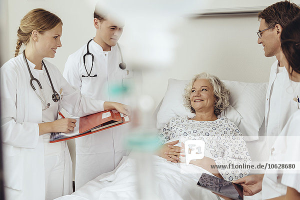 Senior woman in hospital talking to doctors during ward round