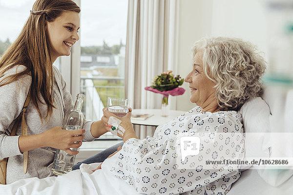 Enkelin besucht Großmutter im Krankenhaus und gibt ihr ein Glas Wasser.