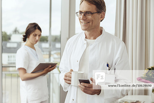 Doctor with coffee cup and smartphone  nurse working in background