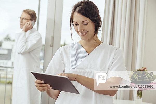 Krankenschwester mit digitalem Tablett im Krankenhauszimmer  Arzt ruft im Hintergrund an