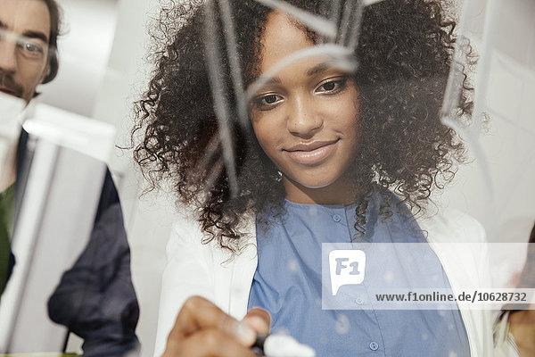 Junge Frau schreibt auf Glaswand im Büro
