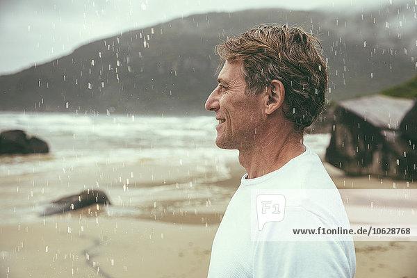 Brasilien  Florianopolis  Profil des glücklichen Mannes  der im Regen am Strand steht.