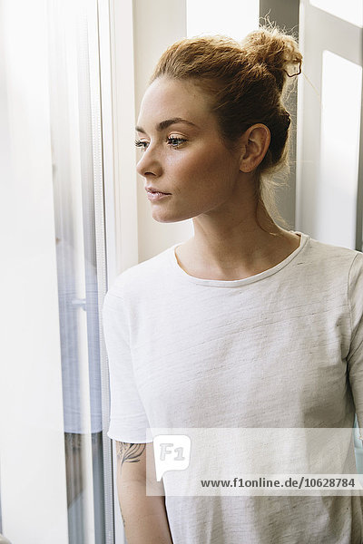 Young woman looking out of her window
