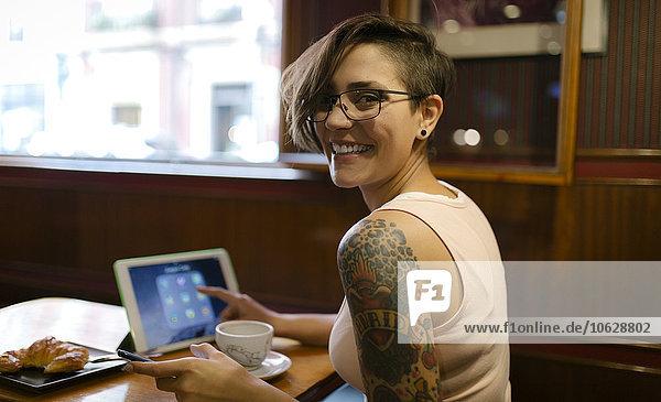 Porträt einer tätowierten jungen Frau  die in einem Coffee-Shop sitzt und ein digitales Tablett benutzt.