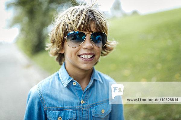 Porträt des blonden Jungen mit blauer Sonnenbrille und Jeanshemd Porträt des blonden Jungen mit blauer Sonnenbrille und Jeanshemd
