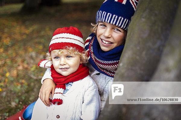 Portrait of two blond boys wearing fashionable knit wear in autumn