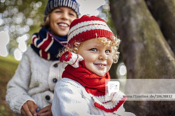 Porträt von blonden kleinen Jungen und seinem Bruder im Hintergrund in modischer Strickmode im Herbst