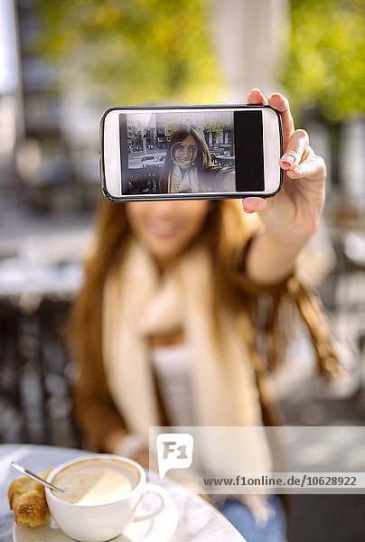 Spain  Gijon  Young woman in cafe taking selfie with smartphone  close up
