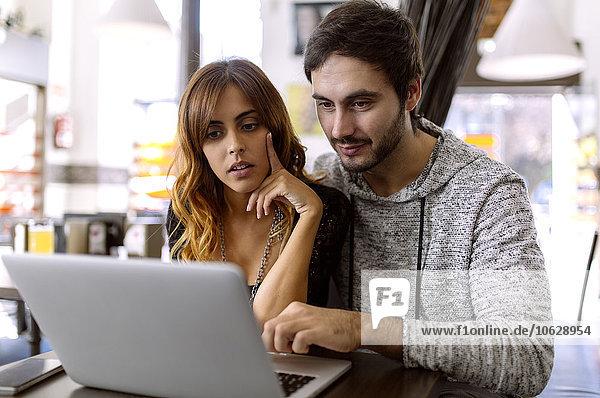 Junges Paar mit Laptop in einer Kneipe