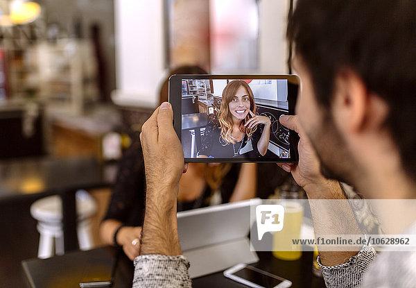 Junger Mann fotografiert seine Freundin mit digitalem Tablett