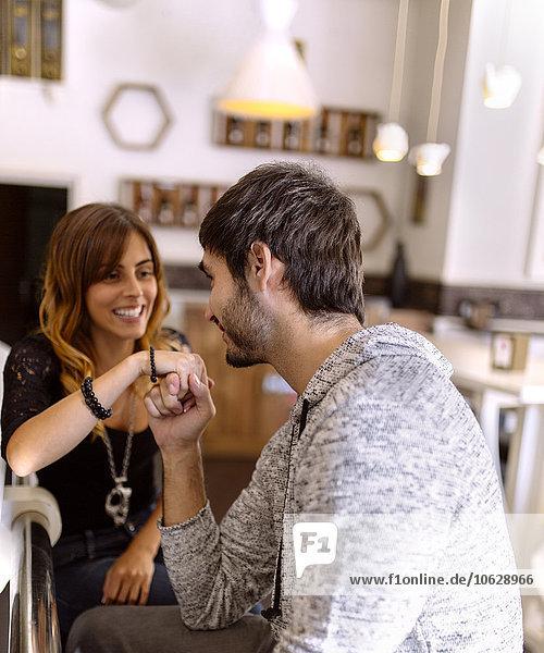 Junger Mann hält Hand seiner Freundin in einer Kneipe