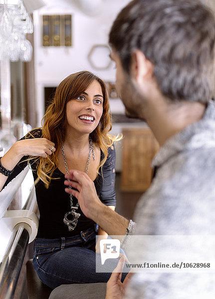 Porträt einer lächelnden jungen Frau mit ihrem Freund in einer Kneipe