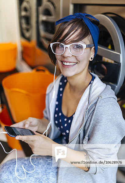 Portrait of smiling young woman hearing music with earphones in a launderette