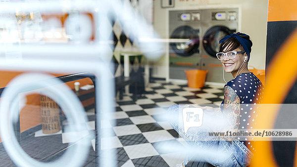 Portrait einer tätowierten jungen Frau  die Musik mit Kopfhörern in einem Waschsalon hört.