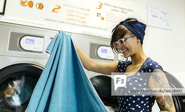 Portrait einer tätowierten jungen Frau im Waschsalon