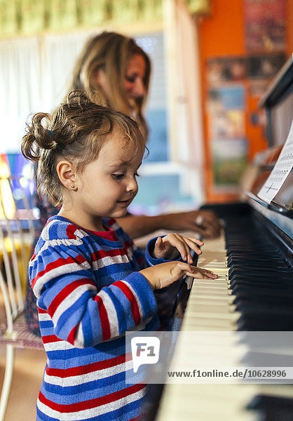 Woman and little girl playing piano together