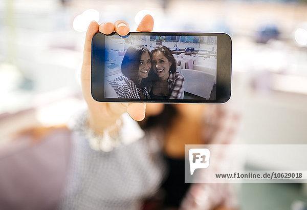 Selfie von zwei lächelnden Freundinnen auf dem Handy-Display