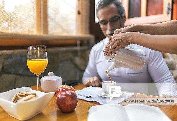 Mann beim Frühstück  während Frau Kaffee in seine Tasse gießt