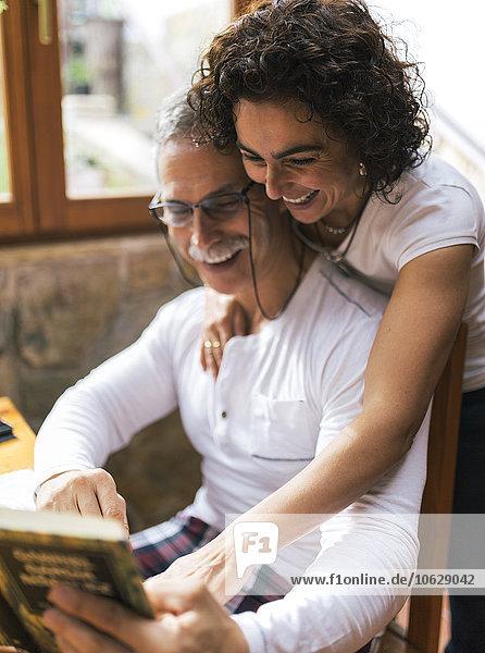 Ein lachendes Paar schaut zusammen auf ein Buch.