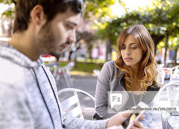 Porträt einer jungen Frau  die ihren Freund mit seinem Smartphone ansieht.