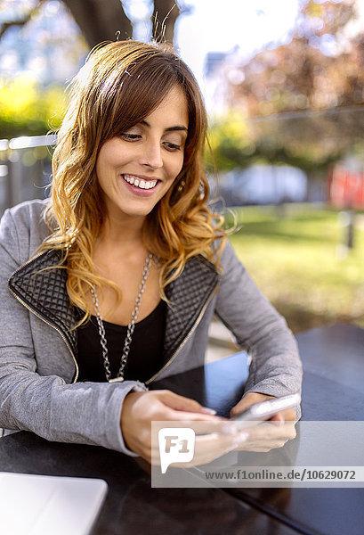 Porträt einer glücklichen jungen Frau  die ihr Smartphone ansieht.