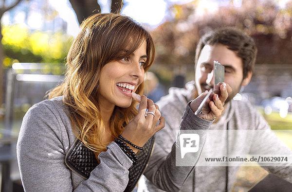Junge Frau  die sich in einem Straßencafé schminkt.