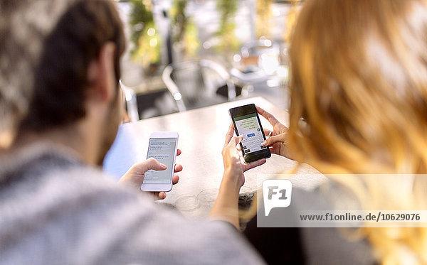 Rückansicht des jungen Paares  das Seite an Seite mit ihren Smartphones sitzt.