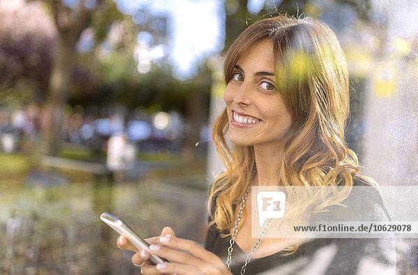 Porträt einer lächelnden jungen Frau mit Smartphone