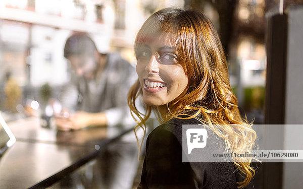 Porträt einer lächelnden jungen Frau  die über die Schulter schaut.