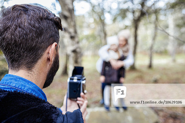 Father taking picture of wife and daughter in the forest