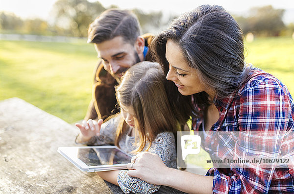 Happy parents with daughter using digital tablet outdoors