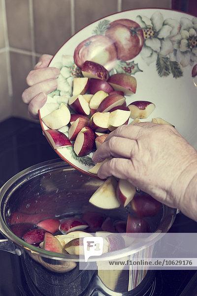Seniorin legt Apfelstücke in einen Kochtopf für die Zubereitung von Apfelmus