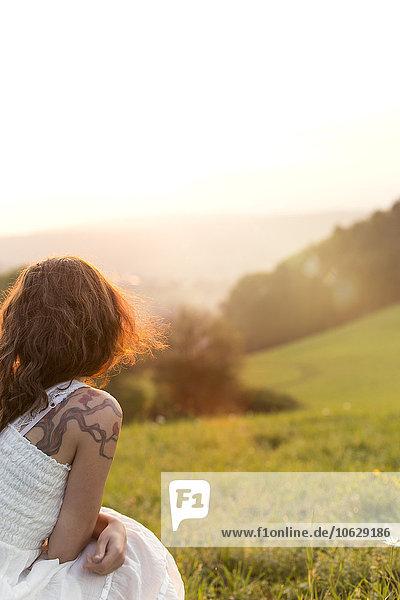 Deutschland  Baden-Württemberg  Schwarzwald  Rückansicht der Frau auf der Alm bei Sonnenaufgang