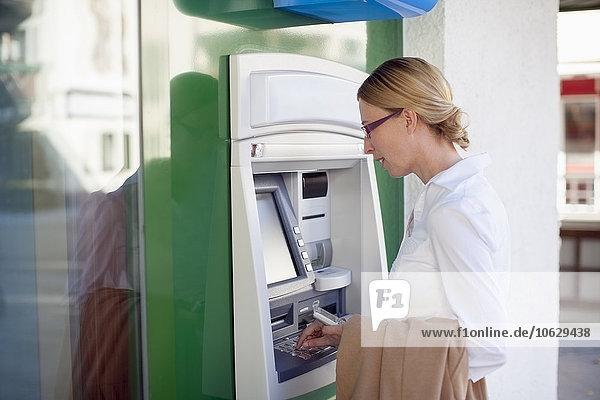 Frau am Geldautomaten