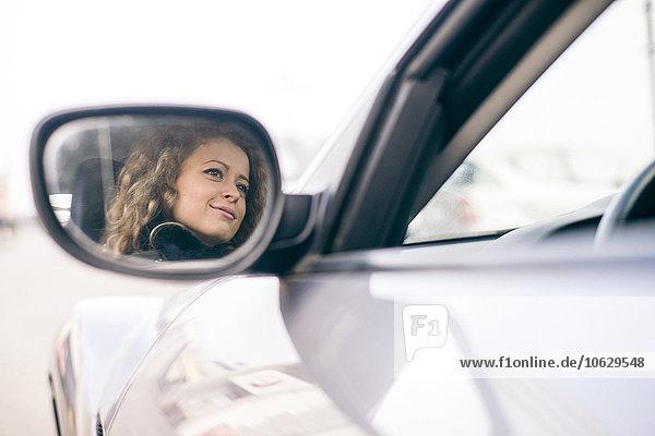 Frau fährt Auto  gespiegelt im Außenspiegel