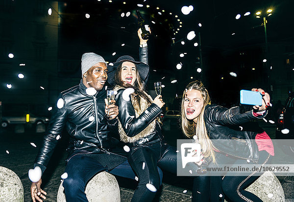 Enthusiastic friends having a party outdoors at night