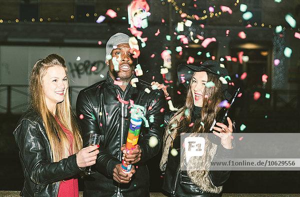 Enthusiastische Freunde bei einer nächtlichen Party im Freien