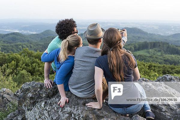 Deutschland  Siebengebirge  Rückansicht von vier Freunden  die einen Selfie mit Smartphone auf dem Mount Olivet nehmen.