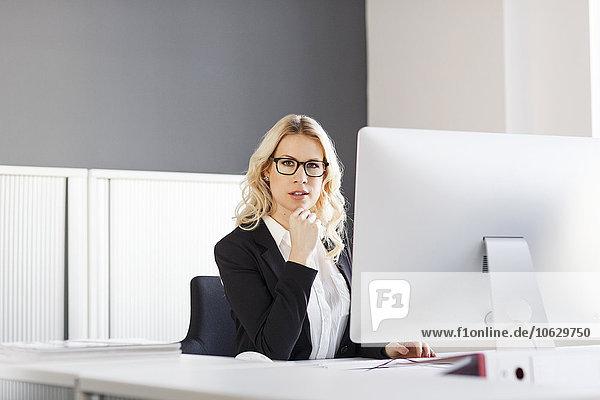 Porträt einer blonden Frau am Schreibtisch im Büro