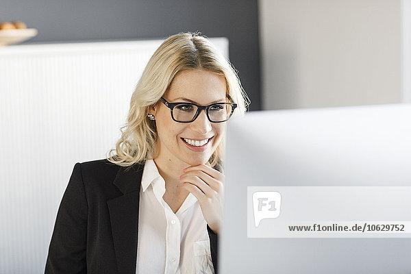 Lächelnde blonde Frau im Büro mit Blick auf den Computerbildschirm