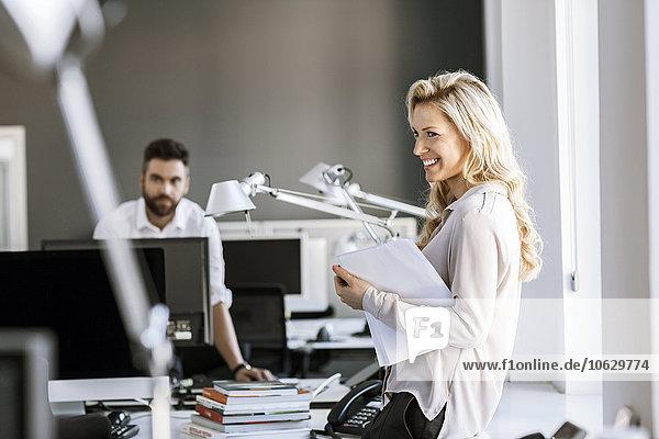 Zwei Kollegen im Büro mit Papieren und Computer