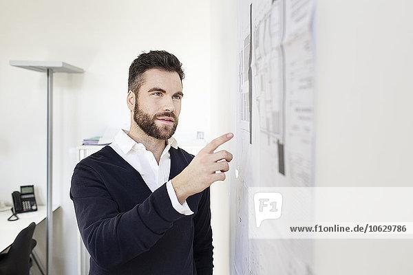 Mann im Büro  der mit Papieren auf die Wand zeigt.