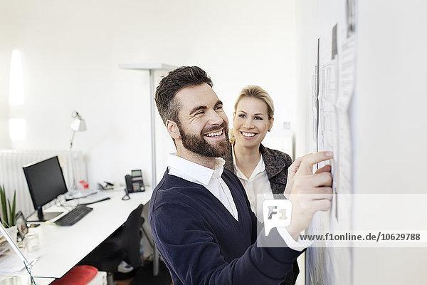 Zwei selbstbewusste Kollegen im Büro an der Wand mit Papieren