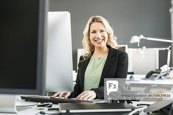 Lächelnde blonde Frau bei der Arbeit am Schreibtisch im Büro