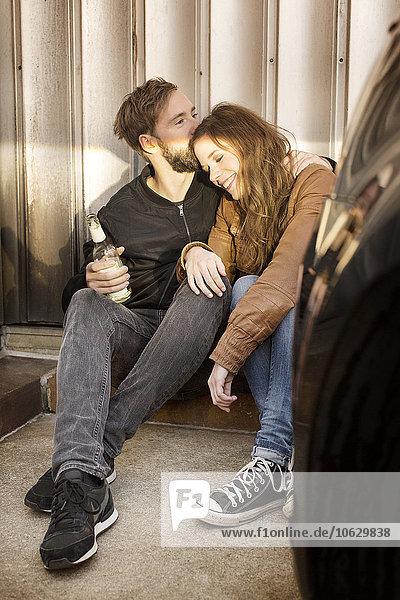 Glückliches Paar mit Bierflasche zum Entspannen in der Garage