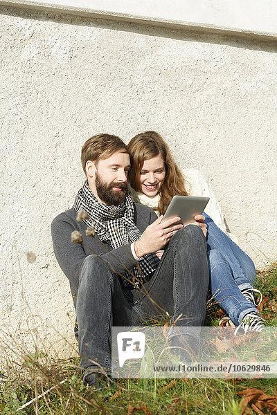 Lächelndes Paar sitzt auf der Wiese und schaut auf ein digitales Tablett.