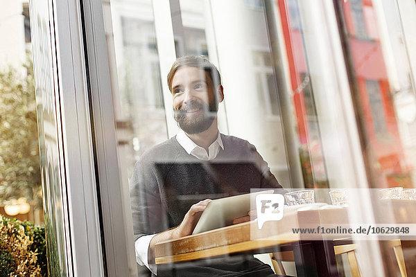 Lächelnder junger Mann mit digitalem Tablett im Restaurant