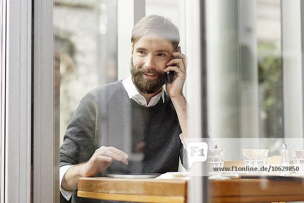 Lächelnder junger Mann am Handy im Restaurant