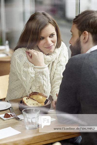Lächelnde junge Frau schaut den Mann am Restauranttisch an.
