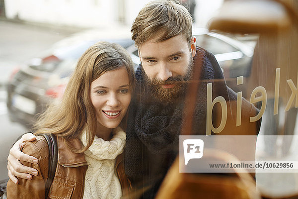Lächelndes junges Paar schaut ins Schaufenster
